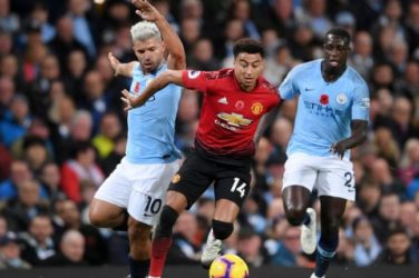 Manchester United's Jesse Lingard is tackled by Sergio Aguero and Benjamin Mendy of Manchester City.