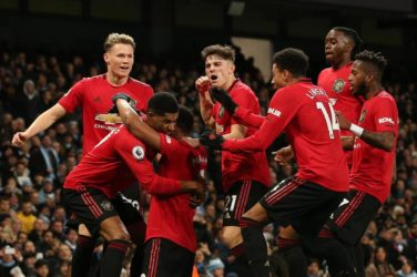 Manchester United celebrate after scoring against Manchester City.