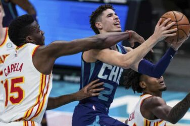 LaMelo Ball finishes at the rim under pressure from Atlanta Hawks' Clint Capela